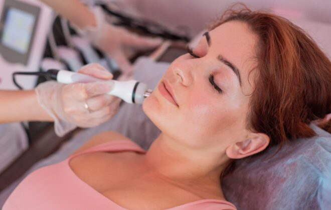 Young redhead woman gets an electric facial massage in the fight against aging. 30 year old woman receives electric ultrasonic facial massage against wrinkles in a beauty salon. Hardware cosmetology